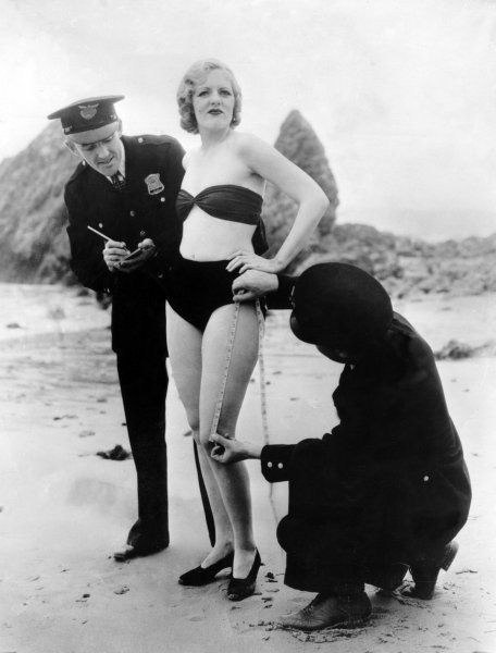 Policemen measuring Peggy Graves' swim suit, to check whether it meets minimum 1933 clothing requirements.